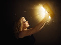 Woman with magic book holding a lights Stock Images