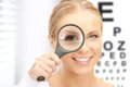 Woman with magnifier and eye chart Royalty Free Stock Photo