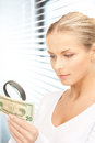 Woman with magnifying glass and money Stock Photography