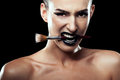 Woman with make up brush in mouth on black background Royalty Free Stock Photo