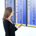 Woman makes check in with smartphone at airport waiting front of a destination board the Stock Photo