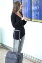 Woman makes check in with smartphone at airport waiting front of a destination board the Stock Image
