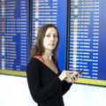 Woman makes check in with smartphone at airport waiting front of a destination board the Royalty Free Stock Photography