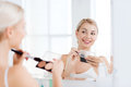 Woman with makeup brush and foundation at bathroom