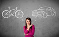 Woman making a choice between bicycle and car Royalty Free Stock Photo