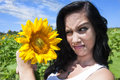 Woman making face at sunflower Royalty Free Stock Photo
