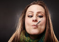 Woman making a funny face while holding a thermometer in her mou closeup of mouth over gray background Royalty Free Stock Photos
