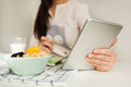 Woman making notes with tablet and healthy food on table Royalty Free Stock Photo