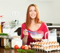 Woman making omlet in kitchen smiling whipping eggs bowl using whisk at her Royalty Free Stock Photography