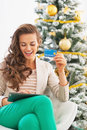 Woman making online shopping with tablet pc near christmas tree happy young in living room Stock Photos
