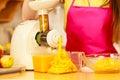 Woman making orange juice in juicer machine Royalty Free Stock Photo