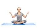 Woman making yoga meditation in lotus pose on mat Royalty Free Stock Photo