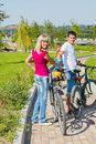 Woman and man with bicycles men in a park Stock Images
