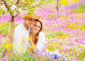 Woman and man on floral field portrait of attractive women handsome men sitting down young lovers having fun in the garden Stock Photos