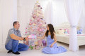 Woman and man hand Christmas presents its half in spacious bedro