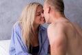 Woman in man`s shirt kissing man