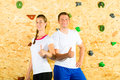 Woman and man standing at climbing wall Stock Photos