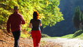Woman and man walking cross country trail in autumn forest Royalty Free Stock Photo