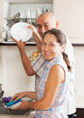 Woman and man washing dishes positive housewife her husband plates with sponge Stock Image