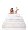 Woman and mattress portrait of a lying on many mattresses orthopedic Royalty Free Stock Images
