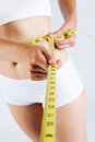 Woman measuring her slim body. Isolated on white background. Royalty Free Stock Photo
