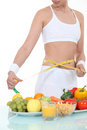 Woman measuring her waist fresh produce Royalty Free Stock Image
