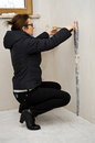Woman measuring in new bathroom using a tape room planning the placement of furniture Royalty Free Stock Images