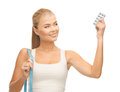 Woman with measuring tape and diet pills sporty Stock Images