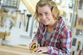 Woman measuring wooden board with tape measure Royalty Free Stock Photo