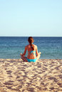 Woman meditating on beach rear view young the summer holiday Stock Image