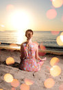 Woman meditating on beach with sun flares Stock Photography