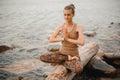 Woman Meditating At The Beach ...