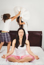 Woman meditating on bed while children playing with pillow Royalty Free Stock Photo