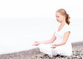 Woman meditating in lotus yoga on beach coast of sea the Stock Photos