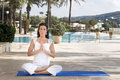 Woman meditating in lotus yoga a middle aged position doing namaste front of hotel pool looking at camera Royalty Free Stock Image