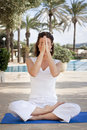 Woman meditating in lotus yoga position with eyes closing holding up hands namaste greeting Stock Photos