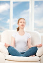 Woman meditating relaxing sitting in a lotus position on the sofa at home against window and sky Royalty Free Stock Images