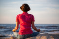 Woman meditating at seaside young meditation on the sunny beach Royalty Free Stock Photo