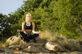 Woman meditating yoga on rock Stock Images
