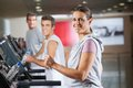 Woman and men running on treadmill in fitness portrait of happy mature women center Royalty Free Stock Images