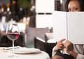 Woman with a menu attractive african descent looking out from the while sitting at the restaurant Royalty Free Stock Images