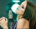 Woman microphone singing beauty model soun studio posing Royalty Free Stock Image