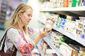 Woman at milk dairy shopping young choosing fresh produces in supermarket store Stock Photos