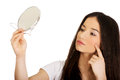 Woman with mirror checking pimples. Royalty Free Stock Photo