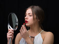 Woman with a mirror and a red lipstick beautiful applying holding Stock Photo