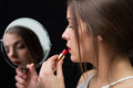 Woman with a mirror and a red lipstick beautiful applying holding Stock Photography