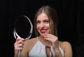Woman with a mirror and a red lipstick beautiful applying holding Royalty Free Stock Photography