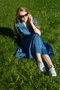 Woman and mobile phone, green lawn, summer. Red hair girl, blue dress, sitting on the grass outside, holding a telephone. Royalty Free Stock Photo