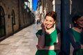 Woman with mobile phone in old city street young beautiful green dress using standing near the windoow on the dubrovnik croatia Royalty Free Stock Image