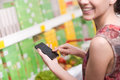Woman with mobile at supermarket Royalty Free Stock Photo